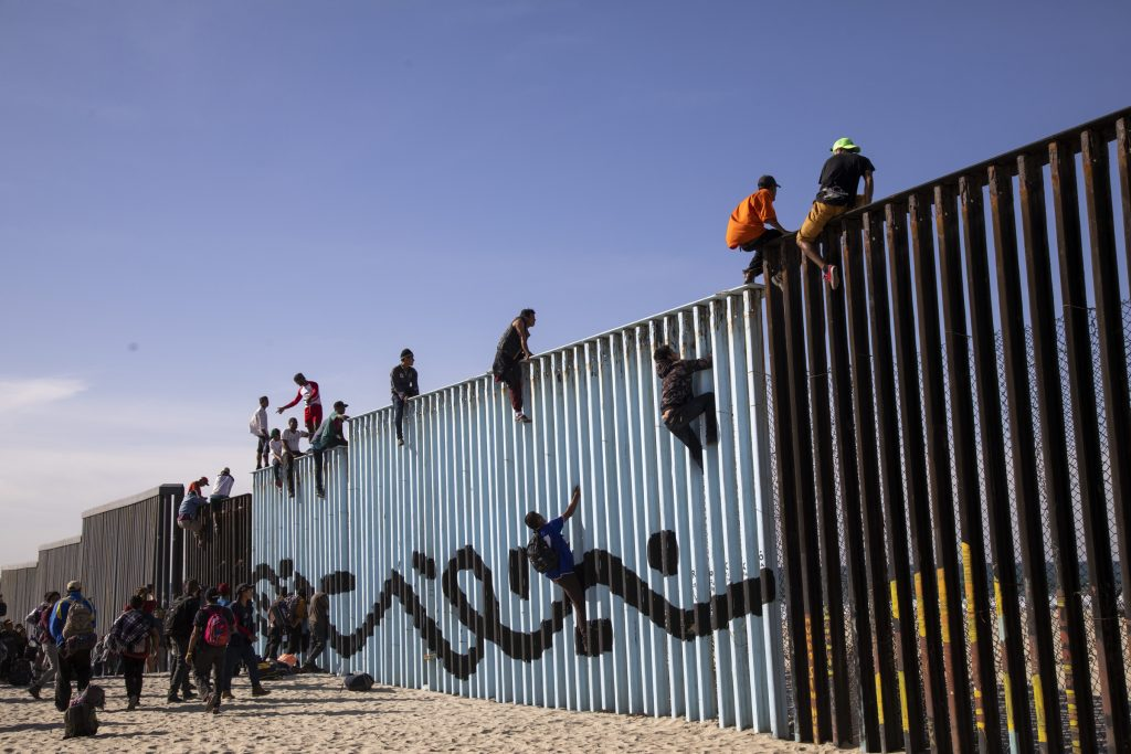 First caravan migrants climb on US fence as hundreds reach Tijuana